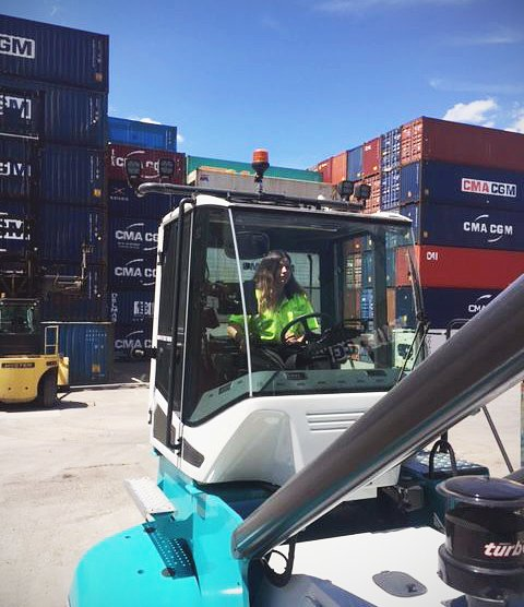 woman driving a forklift in a shipping container yard