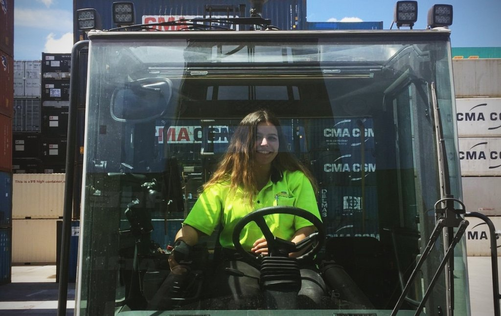 portrait of female forklift operator working for a container shipping company