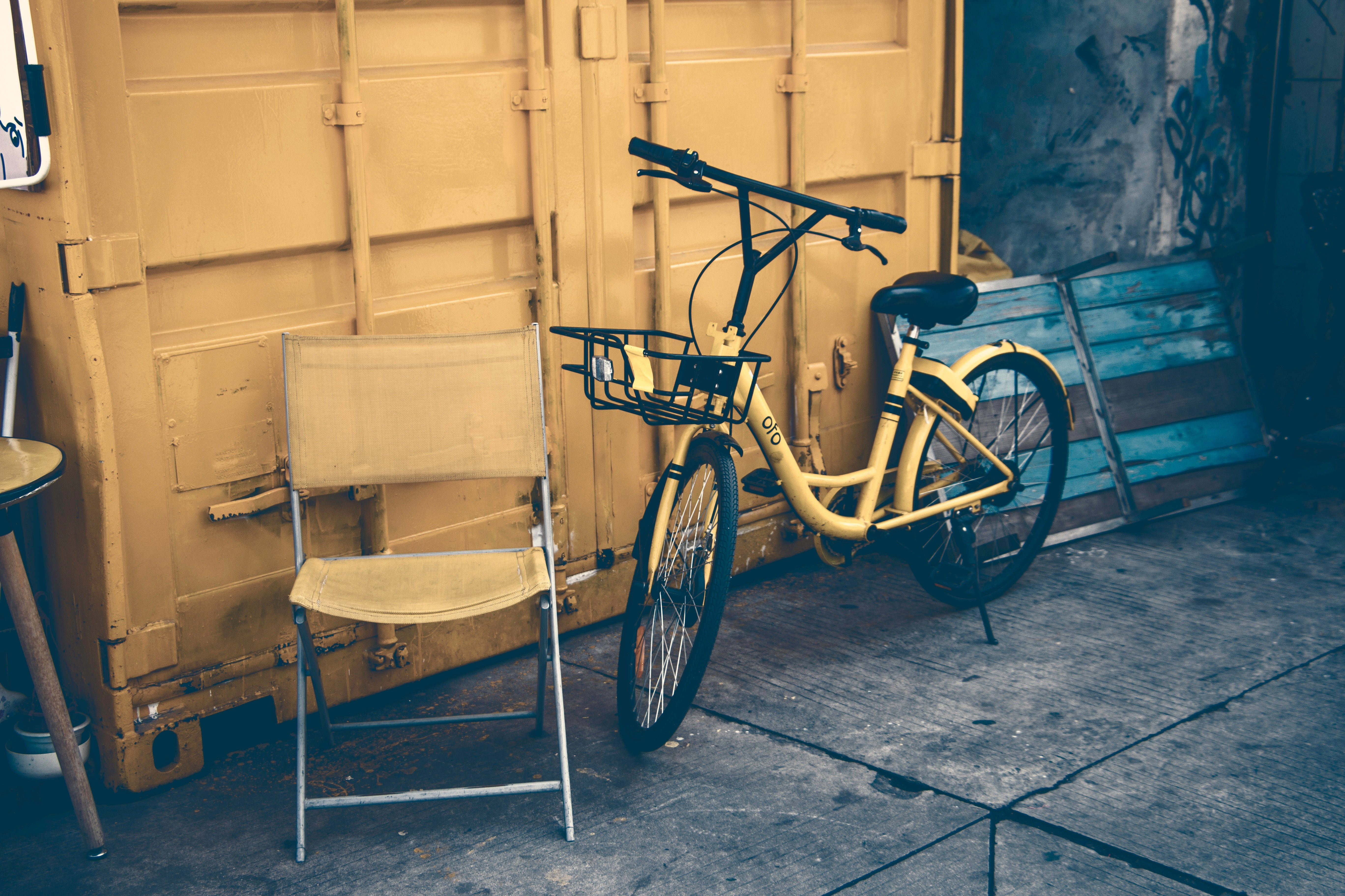 Yellow shipping container with yellow bike and chair